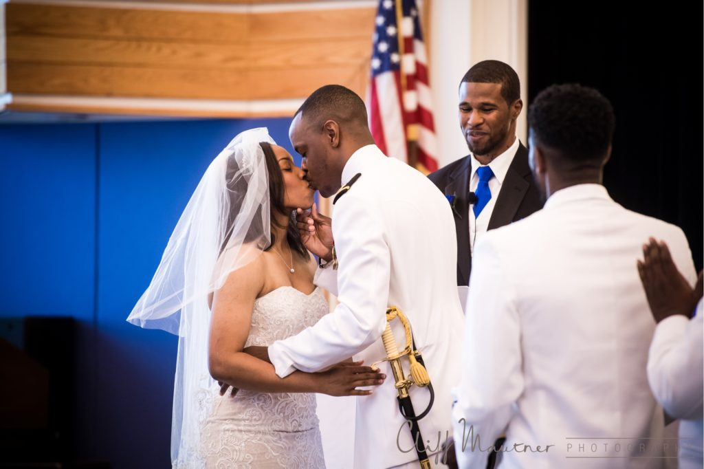 The bride and groom share a kiss to complete the wedding ceremony.