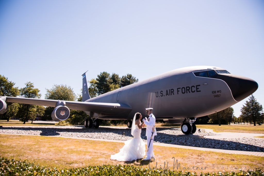 Bride and groom on their wedding day at Fort Dix, New Jersey with a United States Air Force plane in the background.